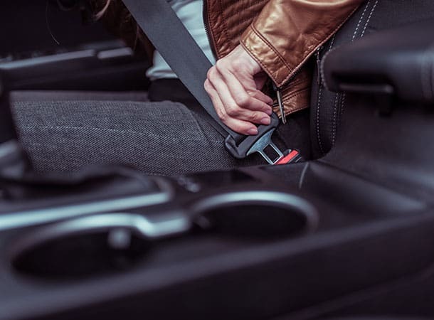 Close-up, a female hand fastens a seat belt in a car, background leather jacket in the summer in spring and autumn, traffic safety in the car.